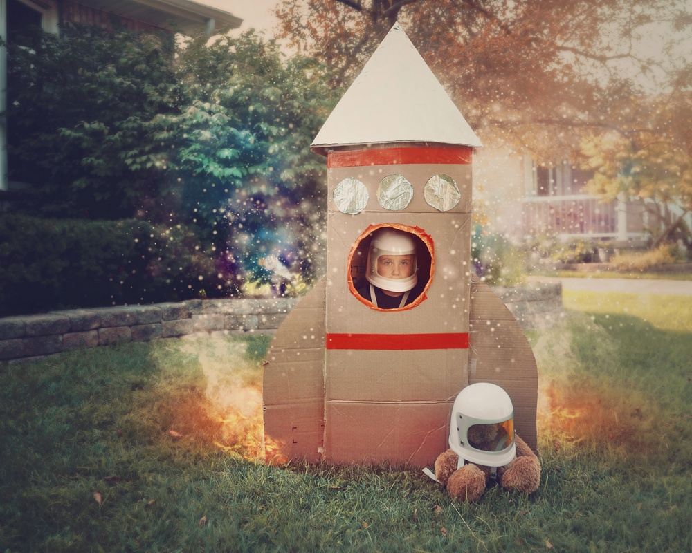 young boy is sitting in a cardboard space rocket ship