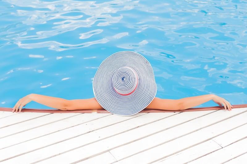 woman in swimming pool wearing large sun hat
